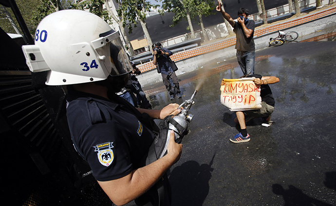 A Turkish riot policeman uses tear gas as a demonstrator holds a banner during a protest against the destruction of trees in a park brought about by a pedestrian project, in Taksim Square in central Istanbul