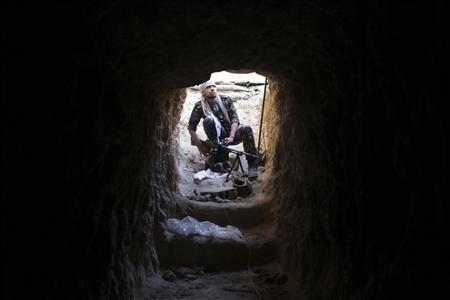 A Free Syrian Army fighter carries his weapon as he takes position inside a tunnel in Deir al-Zor