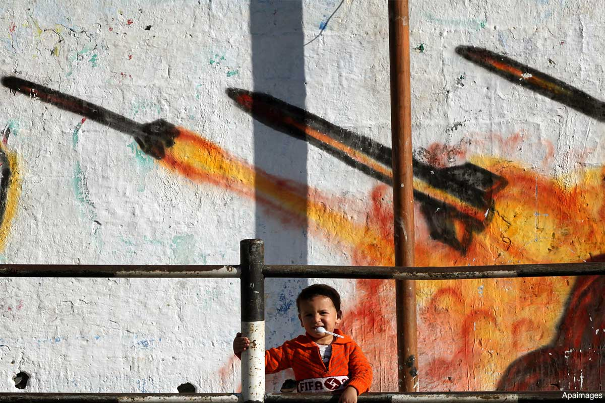 a-palestinian-child-standing-in-front-of-a-mural-to-the-palestinian-resistance-rocket-images-painting