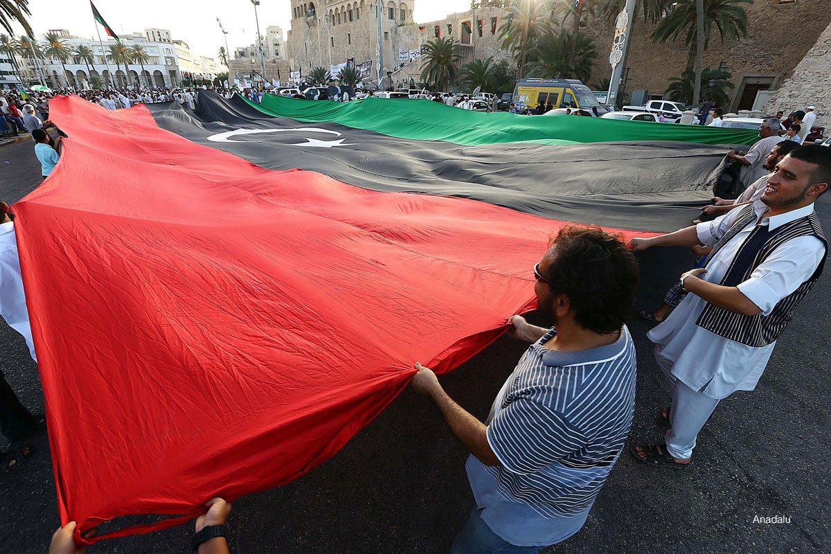 Libyan-protestors-carry-large-flag-through-the-streets