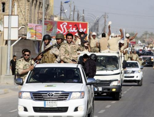 Shi'ite volunteers, who have joined the Iraqi army to fight against the ISIL, parade down a street in Kerbala