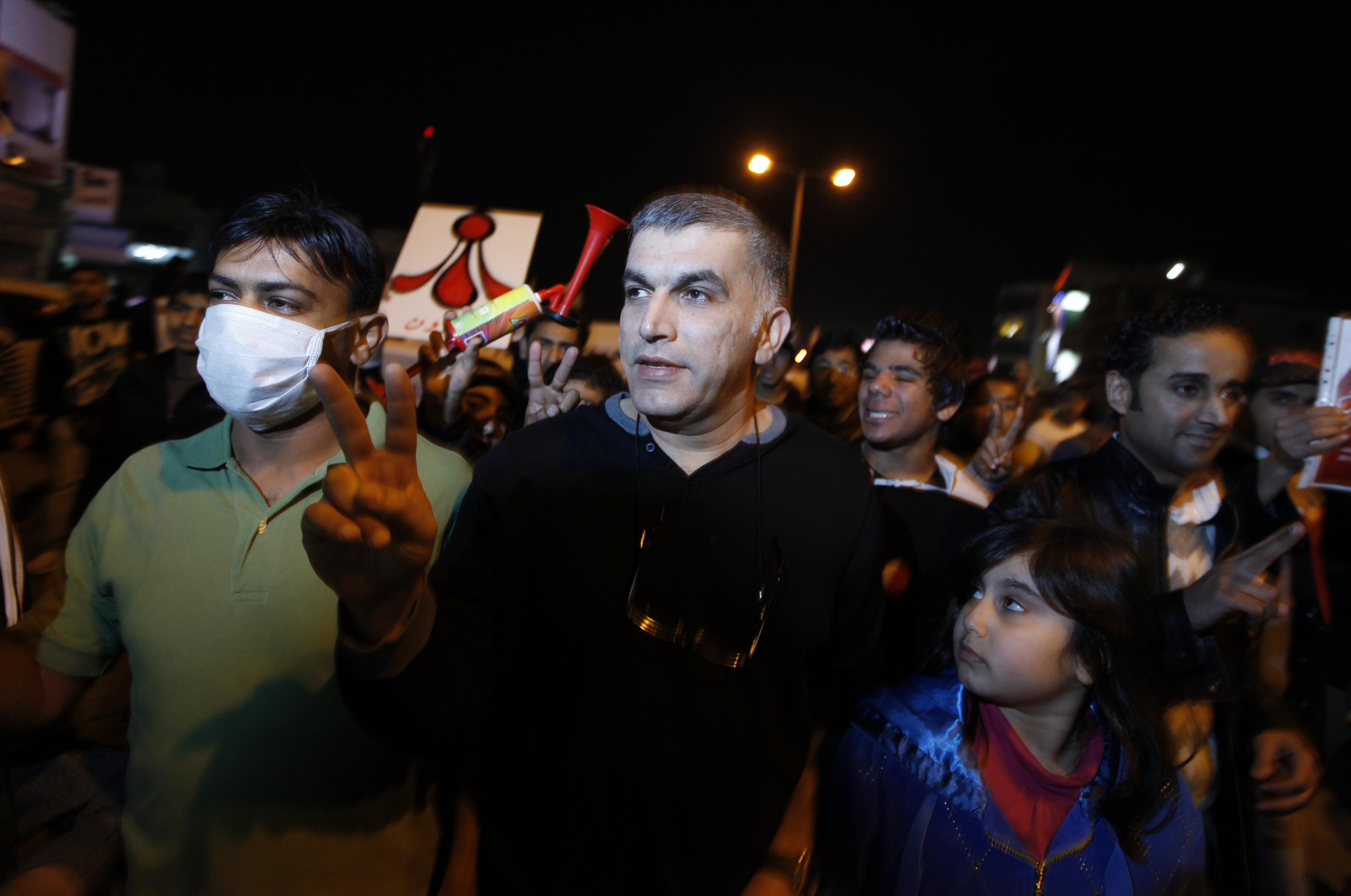 Human rights activist Rajab shows the victory sign as he marches on a highway to participate in a week-long anti-government sit-in in Budaiya