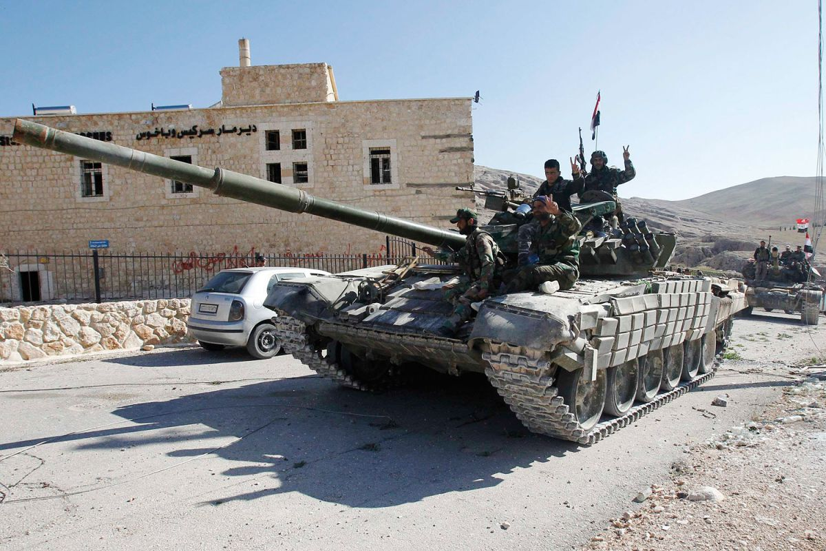 Soldiers loyal to President al-Assad gesture from tank, as they pass Mar Bacchus Sarkis monastery, in Maloula village, northeast of Damascus