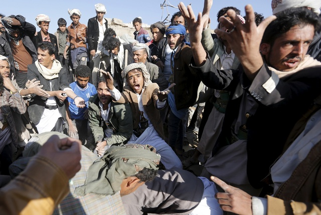 People react as they search for survivors under the rubble of houses destroyed by an air strike near Sanaa Airport