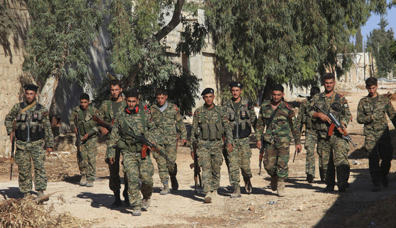 Forces loyal to Syria's President Bashar al-Assad hold their weapons as they walk in Handarat