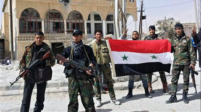 Pro-government forces hold the Syrian flag as they pose for a photo in the village of al-Sahel, near the rebel held town of Yabrud, nearly 80 kilometres north of Damascus, on March 4, 2014.