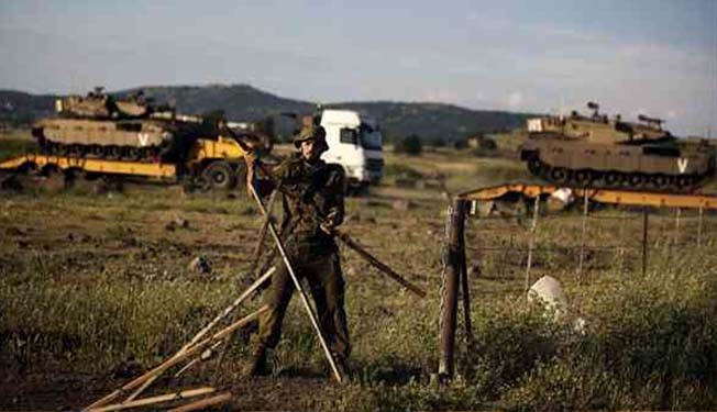 An Israeli soldier closes a gate during a drill in the occupied Golan Heights near the border with Syria on May 5, 2013.