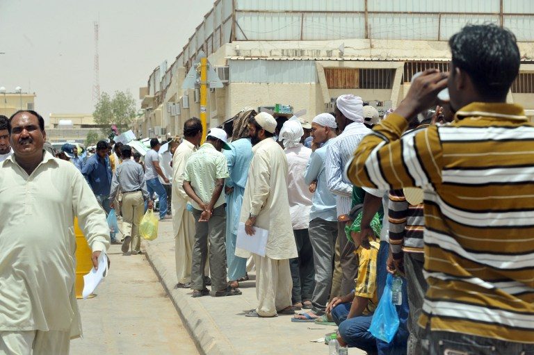 TO GO WITH AFP STORY BY ASSAD ABBOUD  Foreign illegal laborers wait in a queue at the Saudi immigration offices at al-Isha quarter in al-Khazan district west of Riyadh, on June 30, 2013. Some 1.5 million illegal foreign workers in Saudi Arabia, mostly Asians, are in a race against time to take advantage of an amnesty ending July 3, that would allow them to stay or return home without prosecution. AFP PHOTO/FAYEZ NURELDINE