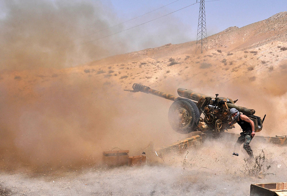 A Syrian army soldier fires artillery shells towards Islamic State (IS) group jihadists in northeastern Palmyra on May 17, 2015. Syrian troops pushed IS group jihadists back from the ancient city of Palmyra, easing fears over the world heritage site, after fighting that left hundreds dead. AFP PHOTO / STR