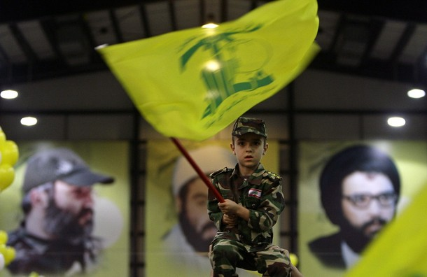 Lebanese boy in military fatigues waves a Hezbollah flag during a ceremony marking the 10th anniversary of Israel's withdrawal from southern Lebanon in southern Beirut on May 25, 2010