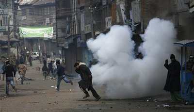 Kashmiri Muslim protesters run for cover as tear gas shell explodes near them during a protest in Srinagar, India, Friday, Dec. 11, 2009. Hundreds of Kashmiris clashed with Indian troops, torching a paramilitary post and hurling rocks, after soldiers fired warning shots and tear gas and beat them with batons to quell anti-India protests in the region's main city. (AP Photo/Dar Yasin)