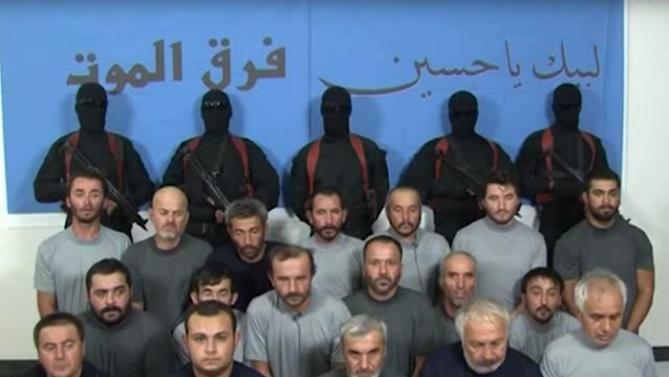 "This image made from a militant video posted on a social media site on Friday, Sept. 11, 2015, which has been verified and is consistent with other AP reporting, purports to show abducted Turkish men seated, as five militants in black masks stand behind them with machine guns, in front of a blue wall emblazoned with the group's alleged name, ""Death Squads"" in Arabic. A video from a previously unknown militant group has surfaced on social media showing 18 Turkish workers abducted in Baghdad last week and threatening Ankara with the ""most violent means."" (Militan Video via AP)"