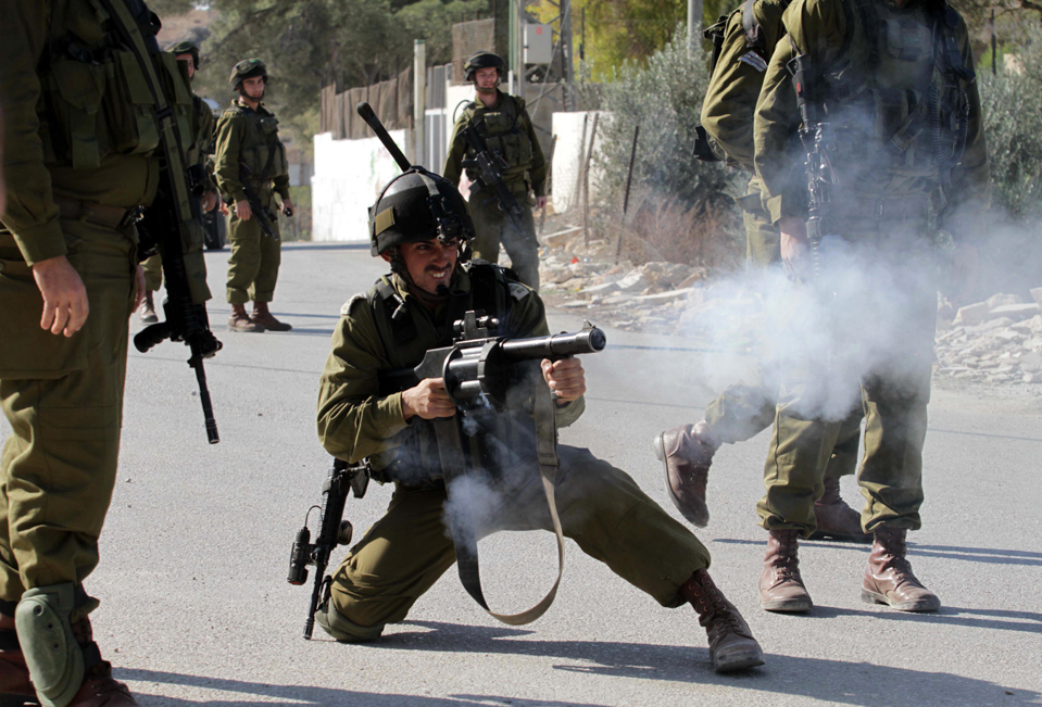 BETHLEHEM, Nov. 19, 2010  An Israeli soldier fires tear gas grenade towards Palestinians and foreign activists during a protest against the Israeli controversial separation barrier in the West Bank village of Al-Masarah, near Bethlehem, on Nov. 19, 2010. (Credit Image: © Xinhua/ZUMAPRESS.com)