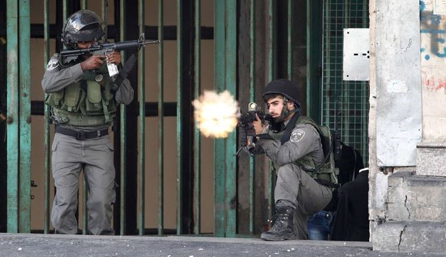 An Israeli border guard Fires towards Palestinian during clashes near an Israeli checkpoint in the West Bank town of Hebron on October 6, 2015.AFP