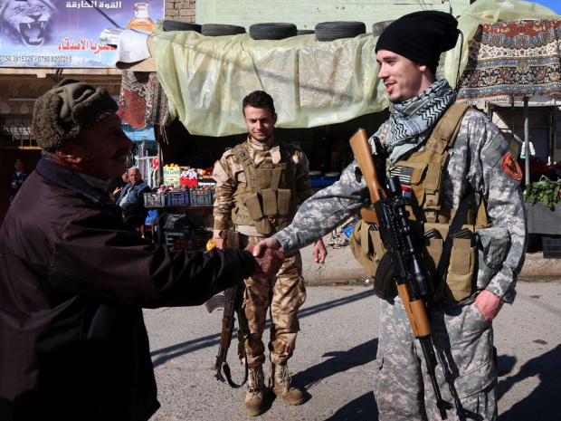TO GO WITH AFP STORY BY JONATHAN KROHN Brett (R), a 28-year-old US national who fights jihadists of the Islamic State (IS) group alongside Dwekh Nawsha, a Christian militia whose name is an Assyrian-language phrase conveying self-sacrifice, shakes hands of a passer-by on February 5, 2015, in the northern Iraqi town of Al-Qosh, located 35 km north of Mosul. The foreign contingent fighting IS is tiny compared to the thousands of foreigners who have joined the jihadist group, but interest is growing and 20 more volunteers already lined up to join. AFP PHOTO / SAFIN HAMEDSAFIN HAMED/AFP/Getty Images