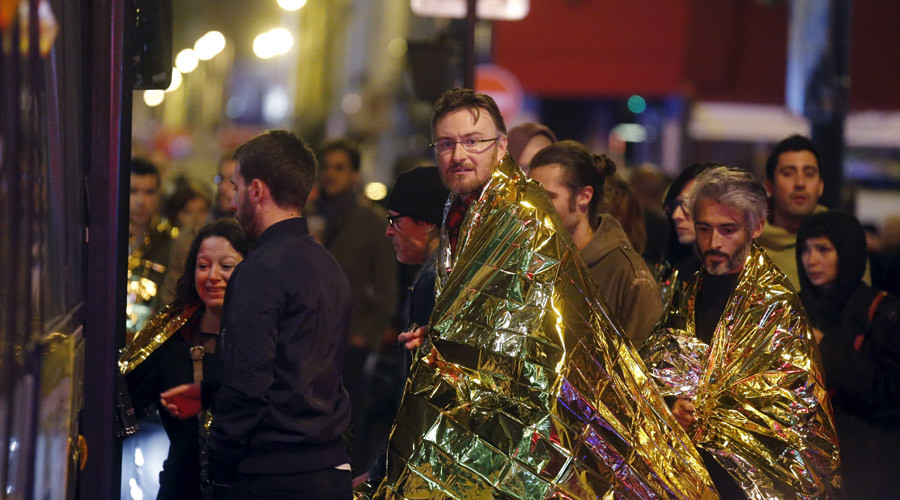 People warm up under protective thermal blankets as they prepare to board a bus to be evacuated near the Bataclan concert hall following fatal attacks in Paris, France, November 14, 2015. Gunmen and bombers attacked busy restaurants, bars and a concert hall at locations around Paris on Friday evening, killing dozens of people in what a shaken French President described as an unprecedented terrorist attack.    REUTERS/Christian Hartmann  - RTS6X6N