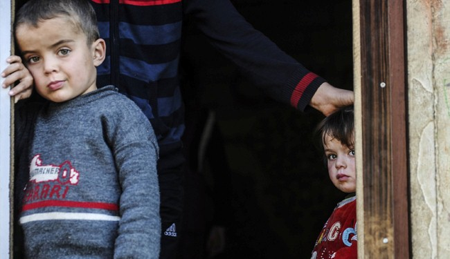 Syrian refugee children look out from their shelter in Hatay, Turkey, on January 20, 2014.