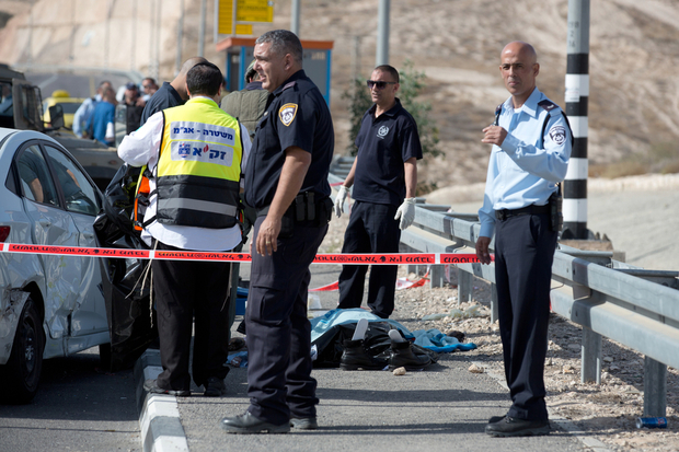 Israeli policemen stand next to a covered body of a Palestinian driver, who attempted to ram a taxi he was driving into civilians and charged at them with a knife before being shot dead, on a highway next the Jewish settlement of Kfar Adumim, located some 10 kms east of Jerusalem in the Judea desert, West Bank, on November 22, 2015. AFP PHOTO / MENAHEM KAHANA / AFP / MENAHEM KAHANA