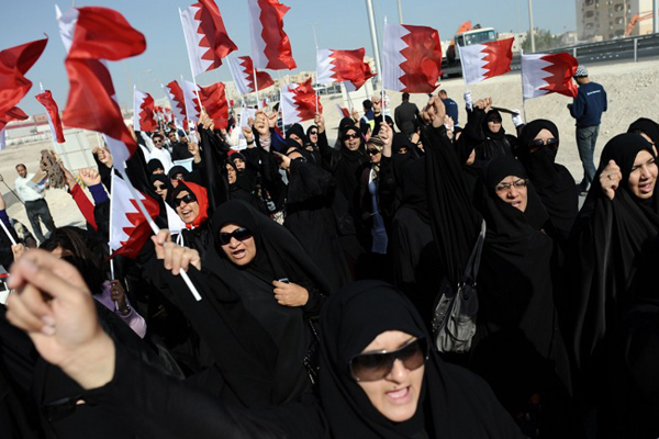 Bahraini women wave their national flag during a rally of Shiite employees who were dismissed from their jobs over pro-democracy protests, near the ministry of labour in Isa Town, south of the capital Manama, on December 27, 2011. AFP PHOTO/STR