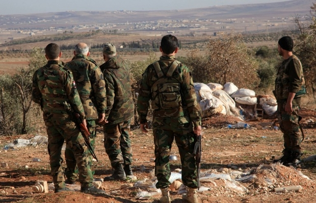 Syrian government forces monitor an area near the village of Khan Tuman, south from the provincial capital Aleppo, on December 22, 2015, two days after army units and other pro-regime forces recaptured several areas in the north of the country from Islamist forces, including Al-Qaeda's Syrian branch, Al-Nusra Front and Ahrar al-Sham brigade. Khan Tuman was the scene of fierce clashes between loyalist forces, including fighters of Lebanon's Shiite militia Hezbollah, and Islamist rebels, said the Syrian Observatory for Human Rights.  AFP PHOTO / GEORGE OURFALIAN / AFP PHOTO / GEORGE OURFALIAN