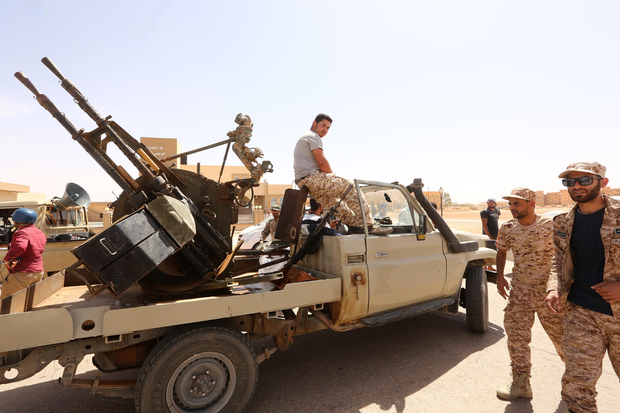 EDITORS NOTE: Graphic content / Libyan pro-government forces walk next to their vehicle mounted with a machine gun on May 18, 2016 in Abu Grein, south of Libya's third city Misrata, a day after Libya's unity government recaptured the area from the Islamic State (IS) group. four of the Bodies of The organization of the Islamic State (Daash) in a truck in Abu Qurayn About 300 km east of the Libyan capital Tripoli , on May 18, 2016. The UN-backed Government of National Accord (GNA) forces said on Facebook that they recaptured  Abu Grein strategic crossroads, where the coastal highway meets the main road south into the desert interior on May 17, 2016.  / AFP PHOTO / MAHMUD TURKIA