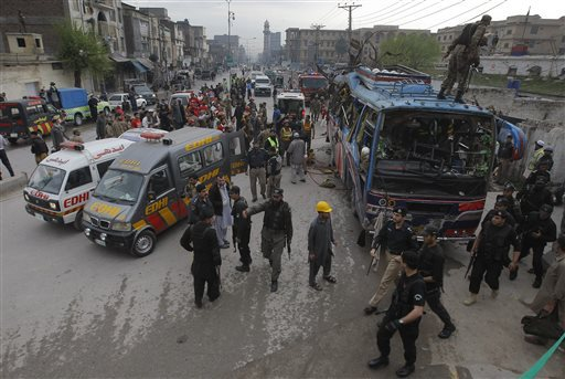 Volunteers and Pakistani security personnel surround a bus following a bomb blast in Peshawar, Pakistan, Wednesday, March 16, 2016. A bomb ripped through a bus carrying Pakistani government employees in the northwestern city of Peshawar on Wednesday, police said. (AP Photo/Mohammad Sajjad)