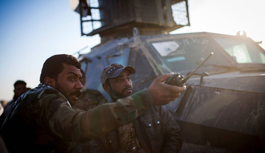 A member of the Hashd Al Shaabi (Popular Mobilisation Units), gives directions to members of his unit after they came under fire by an ISIS snipper at Tal Afar airport on November 20, 2016. Pro-government paramilitary forces advancing on the town of Tal Afar, which commands the city's western approaches, entered its airport, while troops moving up from the south had the Mosul airport in their sights. / AFP PHOTO