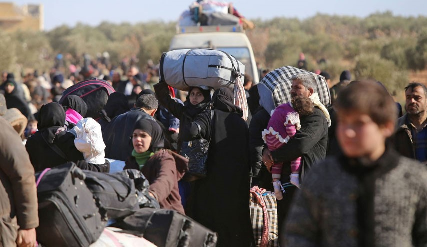 Syrian residents fleeing the violence gather at a checkpoint, manned by pro-government forces, in the village of Aziza on the southwestern outskirts of the northern Syrian city of Aleppo on December 8, 2016. Syria's army battled to take more ground from rebels in Aleppo after President Bashar al-Assad said victory for his troops in the city would be a turning point in the war. / AFP PHOTO