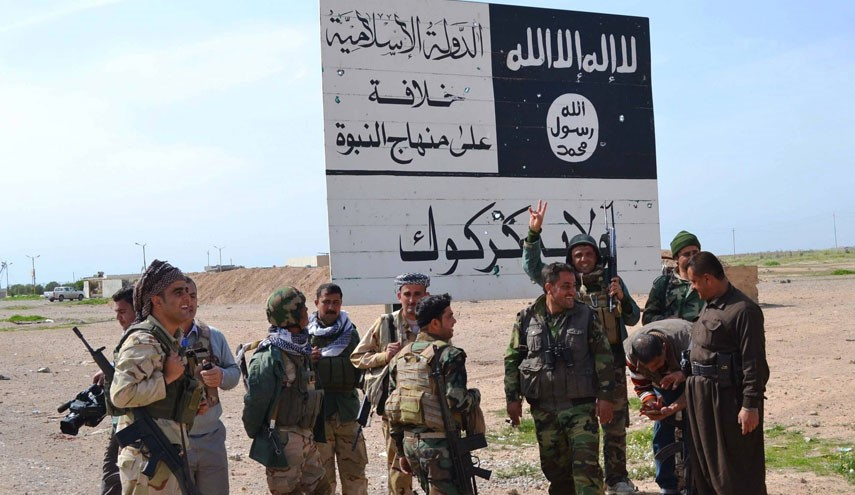 Iraqi Kurdish Peshmerga fighters stand next to an Islamic State (ISIS) group sign at the entrance to the northern Iraqi town of Hawija, south of Kirkuk on March 9, 2015 after they reportedly re-took the area from ISIS terrorists. ISIS spearheaded a sweeping offensive in June 2014 that overran large parts of the country north and west of Baghdad, including in Kirkuk province. AFP PHOTO