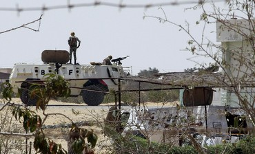 Egyptian soldiers stand guard at a checkpoint in Rafah city on the Egyptian border