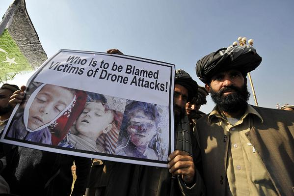 Pakistani tribesmen hold up a placard of