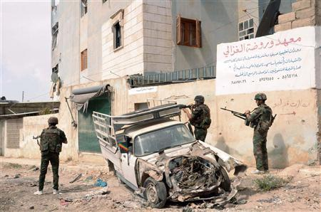 Forces loyal to Syria's President Bashar al-Assad patrol at Tal-al-Zrazir neighbourhood in Aleppo city