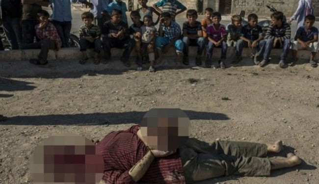Photo of Photo- Terrorists behead pro-gov't Syrians in front of children