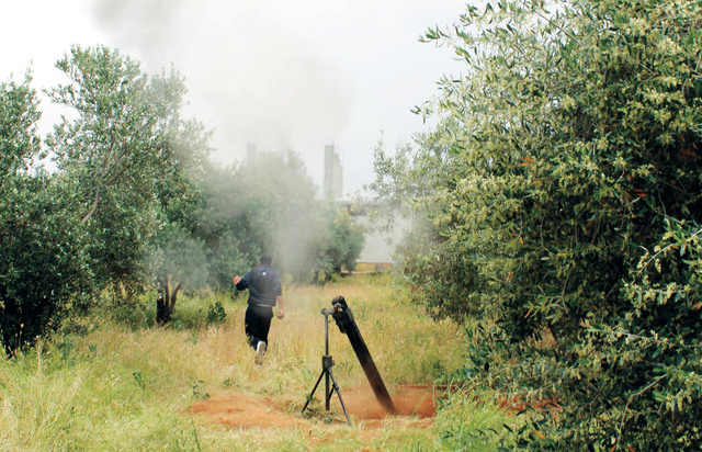 A Free Syrian Army fighter is seen near a mortar in Khirbet Ghazaleh