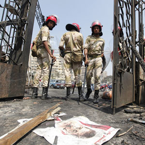 A poster of deposed Egyptian President Mursi lies on the ground as military police stand outside the burnt Rabaa Adawiya mosque in Cairo