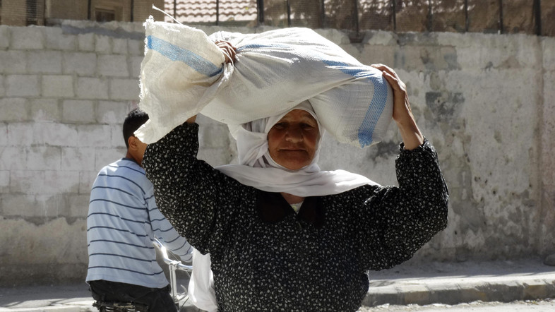 A woman carries a sack of food aid on her head in Ghouta, an eastern suburb of Damascus