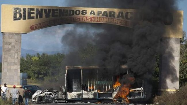 Photo of Mexico townspeople protest, burn trucks