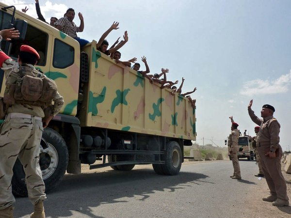 Photo of Iraqi military trucks carry volunteers to a base in Baghdad on Friday