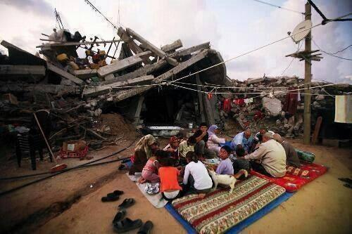 Photo of Gazans breaking fast near their demolished house by zionist israel