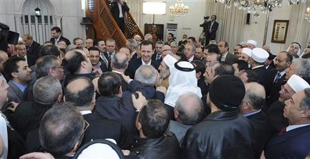Syria's President Bashar al-Assad greets people after attending prayers during celebrations of Prophet Mohammed's birthday at the al-Afram mosque in Damascus