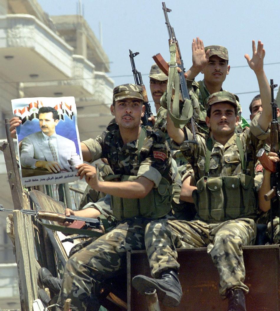 syrian-soldier-displays-poster-president-bashar-al-assad