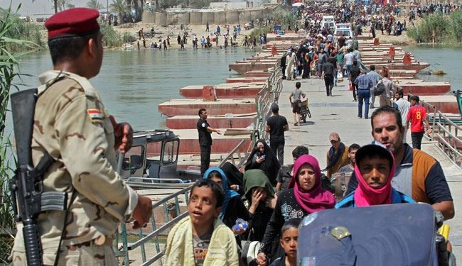 Iraqi security forces stand guard as residents from the city of Ramadi, who fled their homes as ISIS group militants tightened their siege on the capital of Anbar province, wait to cross Bzeibez bridge, on the southwestern frontier of Baghdad, on May 20, 2015.