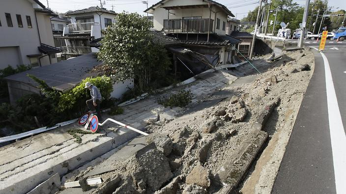 epa05260364 A resident leaps over a traffic sign after checking his house that was damaged by a collapsed national highway in the town of Mashiki, in the Kumamoto Prefecture, southwestern Japan, 15 April 2016, where the strongest earthquake intensity of 7.0 magnitude was registered for the first time since the 2011 Tohoku earthquake and tsunami. Strong earthquakes hit southwestern Japan the evening of 14 April. Authorities said at least nine people died and over 1,000 were injured by the earthquake, now named the Kumamoto Earthquake. Eight of the nine victims were reported in the town of Mashiki. EPA/KIMIMASA MAYAMA