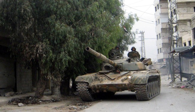 A picture taken on November 7, 2013, shows an army tank driving through the streets of Sbeineh south of Syrian capital Damascus.