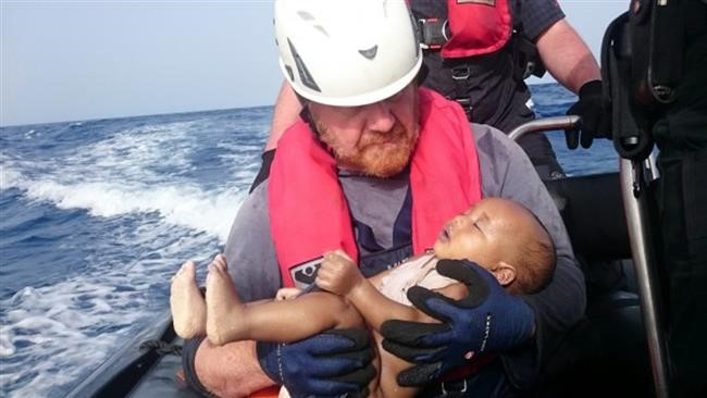 A German rescuer from the humanitarian organization Sea-Watch holds a drowned refugee baby, off the Libyan cost May 27, 2016. (Reuters)