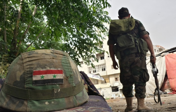 A Syrian soldier stands near an army helmet decorated with the Syrian flag in the Jab al-Jandali district of the central city of Homs on May 7, 2014 after Syrian government forces regained control of the city. The evacuation of rebel-held ts of Syria's Homs began today under an unprecedented deal which hands back control to the government weeks before the controversial June 3 election expected to return President Bashar al-Assad to office. AFP PHOTO/STR