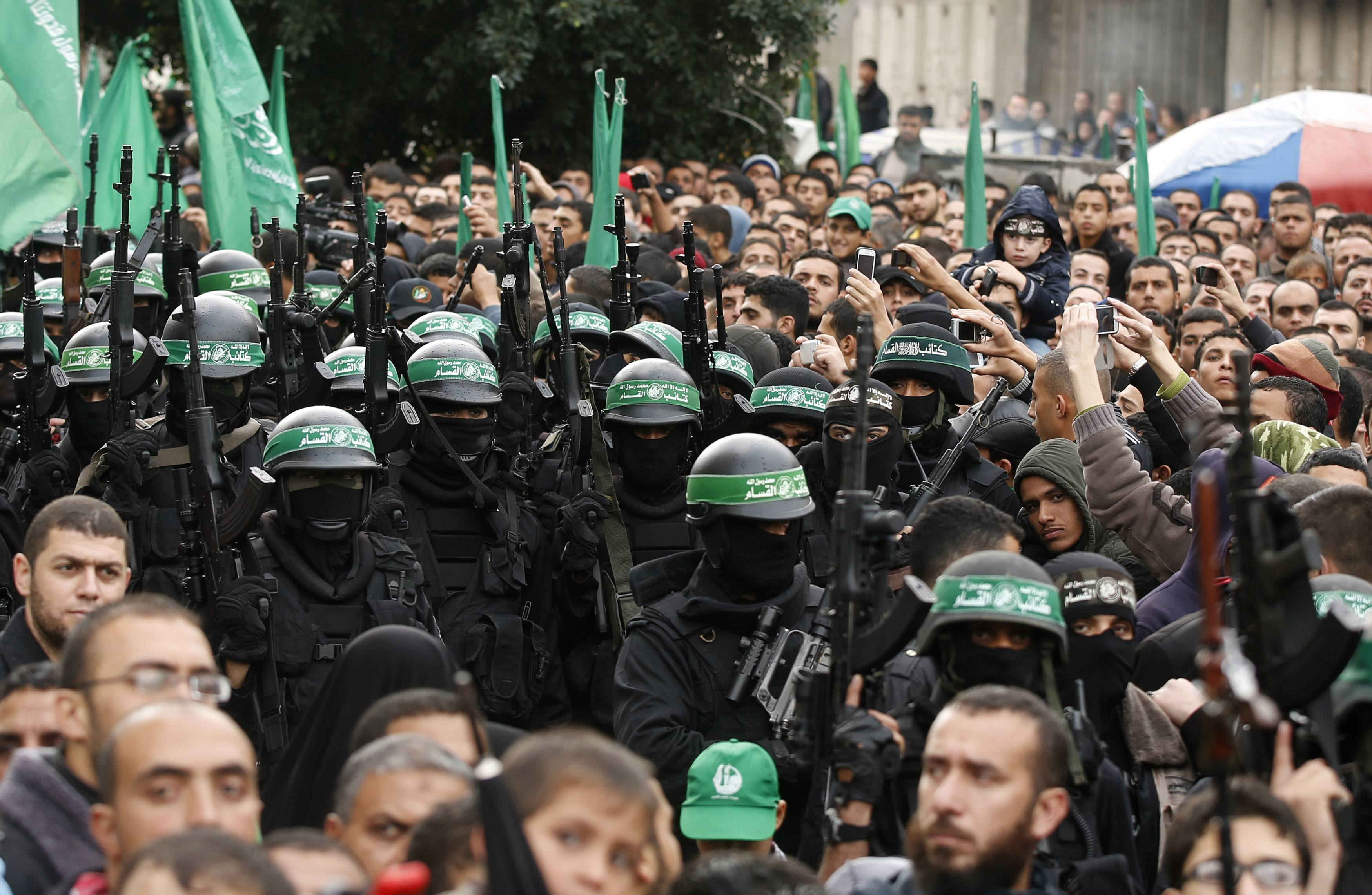 People watch as Palestinian members of al-Qassam Brigades, the armed wing of the Hamas movement, take part in a military parade marking the 27th anniversary of Hamas' founding, in Gaza City December 14, 2014.  REUTERS/Mohammed Salem