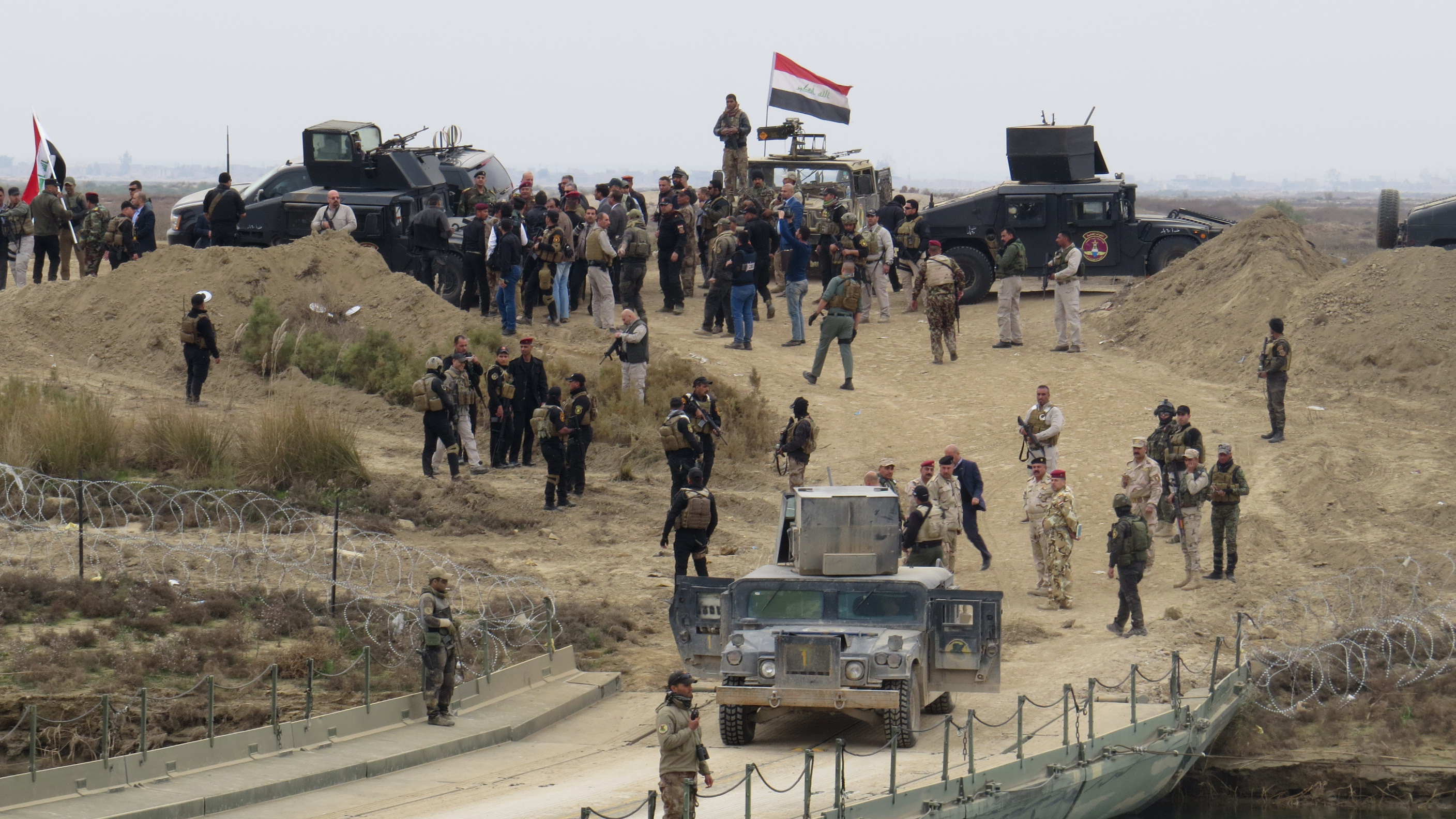 Iraqi security forces gather near a temporary bridge built by the corps of engineers in the Iraqi army south of Ramadi, during a visit by Iraqi Prime Minister Haider al-Abadi on December 29, 2015, after government forces recaptured the city from the Islamic State jihadist group. Abadi visited Ramadi, which lies around 100 kilometres (60 miles) west of Baghdad and is the capital of the province of Anbar, a day after federal forces announced the liberation of the city from the Islamic State group, clinching a landmark victory.  AFP PHOTO / STR / AFP / STR        (Photo credit should read STR/AFP/Getty Images)