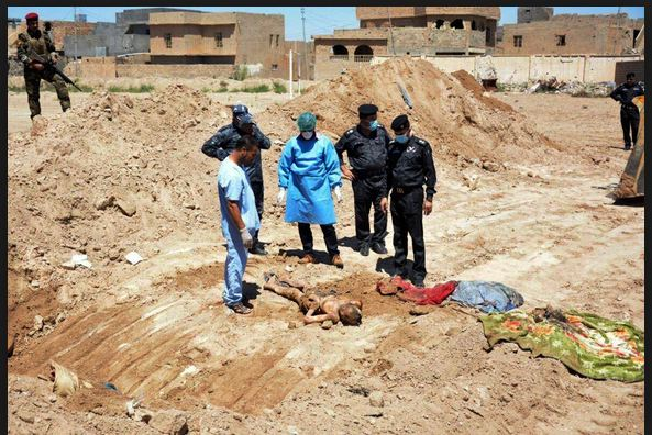 Photo of Iraqi investigators examine mass grave site near Mosul