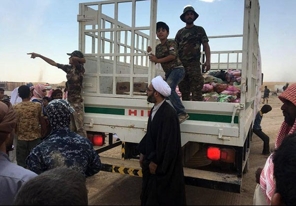 Photo of Photos- Hashd Al-Shaabi Provides Humanitarian Aid to Displaced Families of Mosul